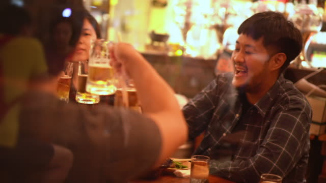 toasting at nightout in izakaya resturant bar in japanese culture - catering building stock videos & royalty-free footage