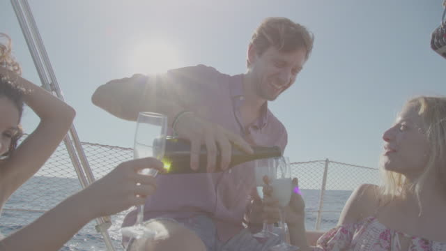 Toasting together on a yacht sailboat cruising the sea