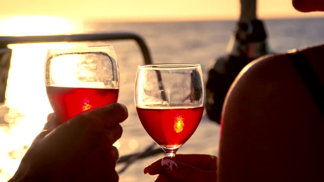CU Toasting Wine Glasses On A Sailboat At Sunset