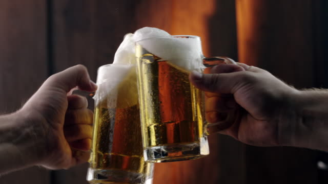 toasting with beer mugs - celebratory toast stock videos & royalty-free footage