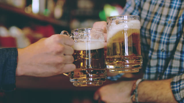 slo mo toasting with beer - celebratory toast stock videos & royalty-free footage