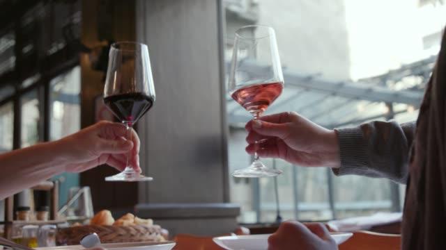 vídeos de stock, filmes e b-roll de brindando com vermelho e rosa vinho em um restaurante - taça de vinho