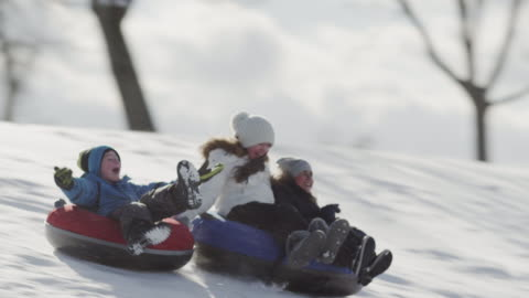 tobogganing on a hill with friends - vacations stock videos & royalty-free footage