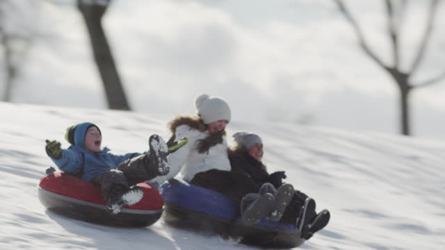 tobogganing on a hill with friends - recreational pursuit stock videos & royalty-free footage
