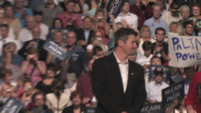 Todd Palin standing on stage with supporters behind him while his wife Republican Governor Sarah Palin speaks at campaign event on September 9 2008 /...