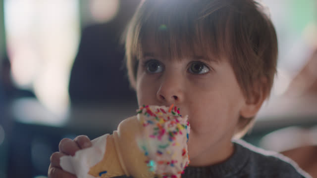 slo mo. cu. a toddler aged boy eats a vanilla ice cream cone covered with sprinkles - spice stock videos & royalty-free footage