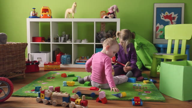 ws ds toddler (12-23 months) and girl (4-5) playing in room / potsdam, brandenburg, germany - spielzeug stock-videos und b-roll-filmmaterial