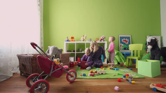 vídeos de stock, filmes e b-roll de ws toddler (12-23 months) and girls (4-6) playing in room / potsdam, brandenburg, germany - brinquedo