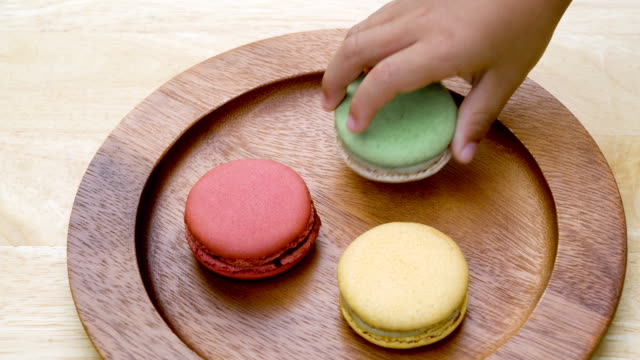 toddler and parent's hand picking macarons. - french food top view stock videos & royalty-free footage