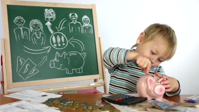 幼児およびピギー銀行 - 金銭に関係ある物点の映像素材/bロール