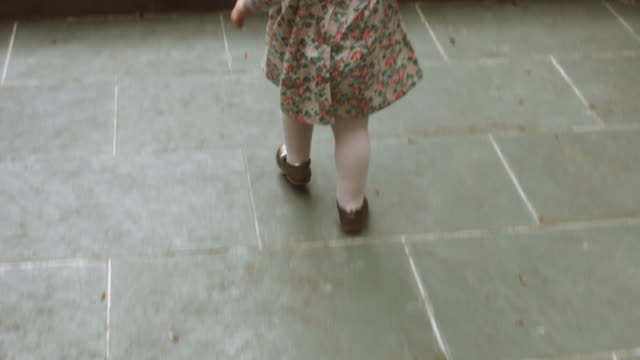 Toddler at home walking with watering can