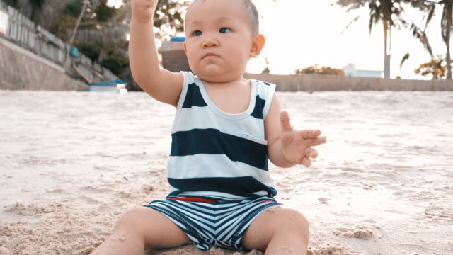 vídeos de stock, filmes e b-roll de menino bebê brincando de areia na praia - 6 11 months