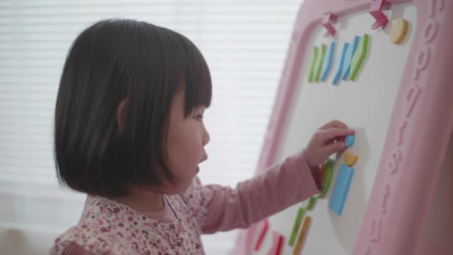 stockvideo's en b-roll-footage met peuter baby meisje spelen vorm speelgoed blok op het witte bord kou witte achtergrond - blok vorm