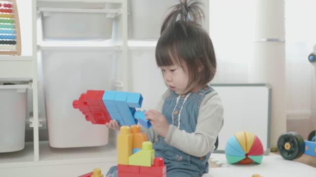 幼児の赤ちゃん女の子再生グッズ ブロック自宅 - 気にかける点の映像素材/bロール