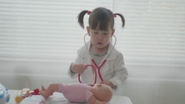 toddler baby girl pretend playing as a doctor at home - baby girls stock videos & royalty-free footage