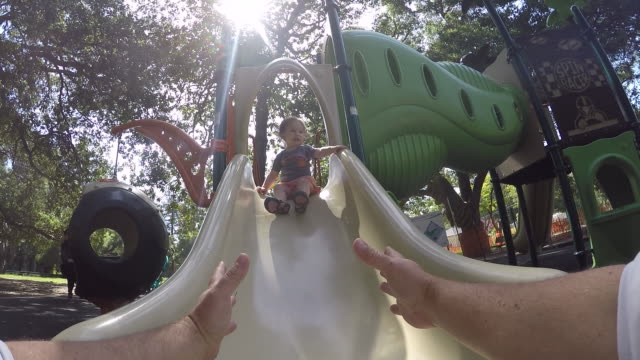 vídeos de stock, filmes e b-roll de a toddler baby going down a slide on a sunny day in the park. - pegar
