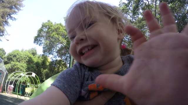 stockvideo's en b-roll-footage met a toddler baby going down a slide on a sunny day in the park. - glijbaan speeltuintoestellen