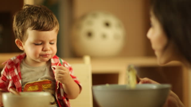 vídeos de stock, filmes e b-roll de toddler boy eating noodles with his mother - bebês meninos