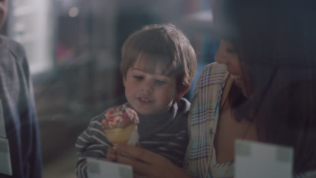 toddler boy gets an ice cream cone and takes a big bite with his family - toddler stock videos & royalty-free footage