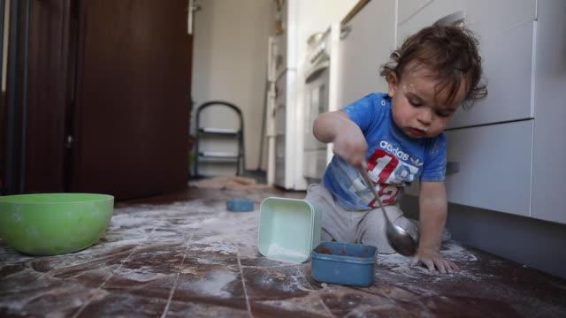 vídeos de stock e filmes b-roll de toddler boy having fun with flour at kitchen - messy