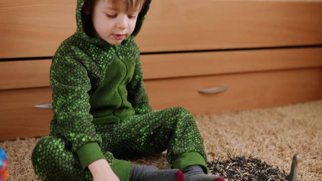 stockvideo's en b-roll-footage met de jongen van de peuter in een dinosauruskostuum dat met zijn dinosaurussen speelt - jura mesozoïcum