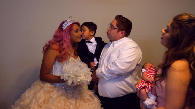 ms toddler boy kissing young woman in quinceanera gown on cheek while standing in home before ceremony - 14 15 anni video stock e b–roll
