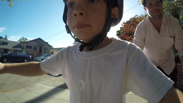 vidéos et rushes de a toddler boy learning to ride his bicycle outside on a sunny day in a residential neighborhood. - casque de vélo