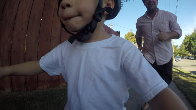 a toddler boy learning to ride his bicycle outside on a sunny day in a residential neighborhood. - sports helmet stock videos and b-roll footage