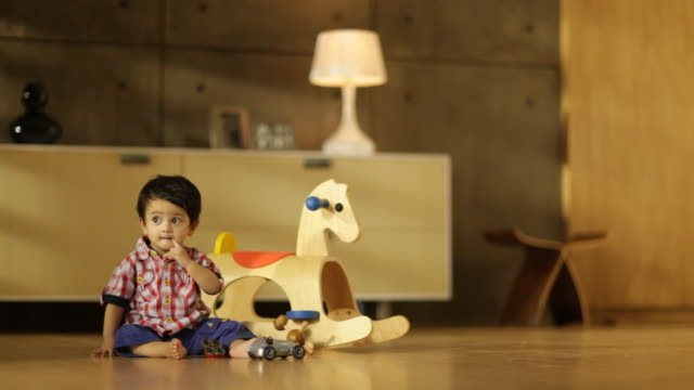 Toddler boy next to rocking horse in living room