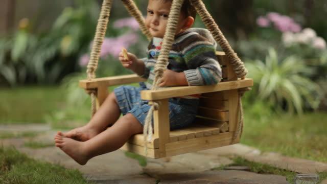 toddler boy on tree swing - ein männliches baby allein stock-videos und b-roll-filmmaterial