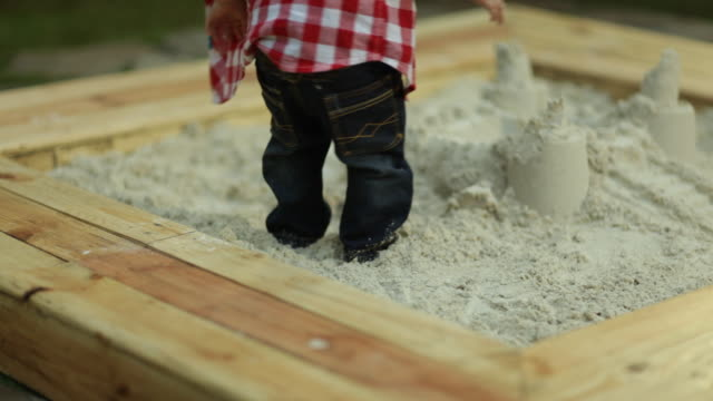 toddler boy playing in garden sand pit - sand pit stock videos and b-roll footage