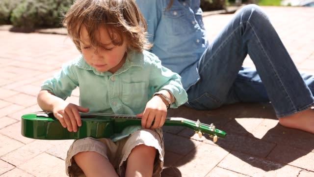 toddler boy playing ukulele
