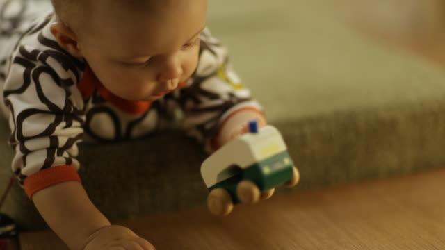 vídeos y material grabado en eventos de stock de toddler boy playing with toys on a seating bench in living room - sólo niños bebés