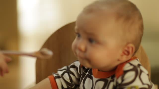 vídeos y material grabado en eventos de stock de toddler boy playing with toys on a seating bench in living room - comida de bebé