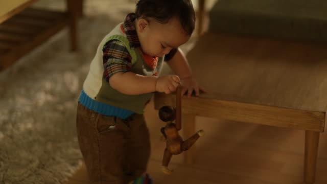 vídeos y material grabado en eventos de stock de toddler boy playing with wooden monkey toy on living room floor - sólo niños bebés