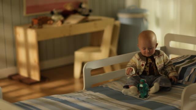vídeos y material grabado en eventos de stock de toddler boy sitting on a bed playing with a tin robot - sólo niños bebés