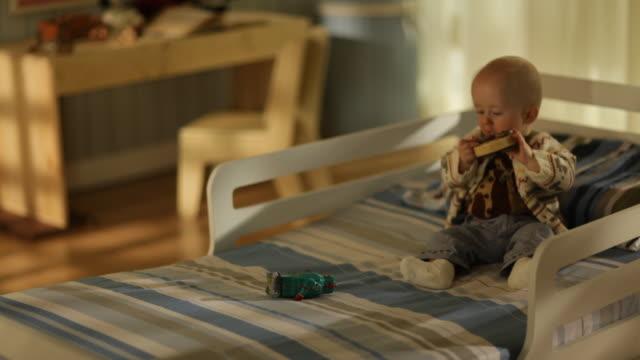 vídeos y material grabado en eventos de stock de toddler boy sitting on a bed playing with toys - sólo niños bebés