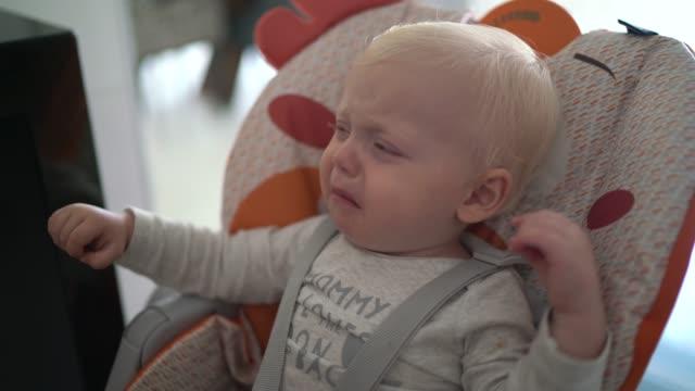 vídeos de stock, filmes e b-roll de menino criança sentado na cadeira alta chorando - olhos azuis