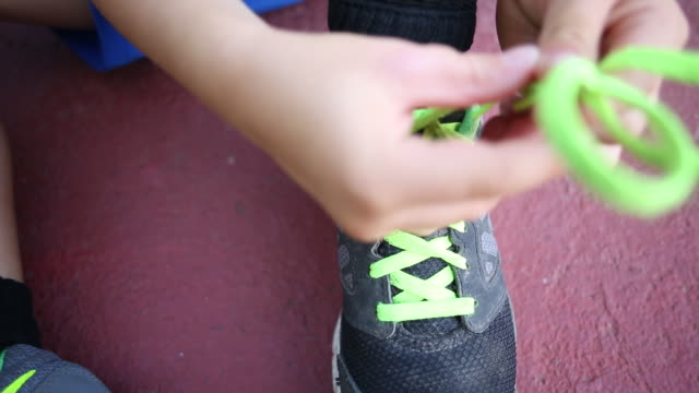 A toddler boy trying to tie his shoelaces outdoors on the pavement.