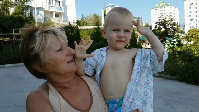 toddler boy walking with beloved grandmother outdoors - baby boys stock videos and b-roll footage