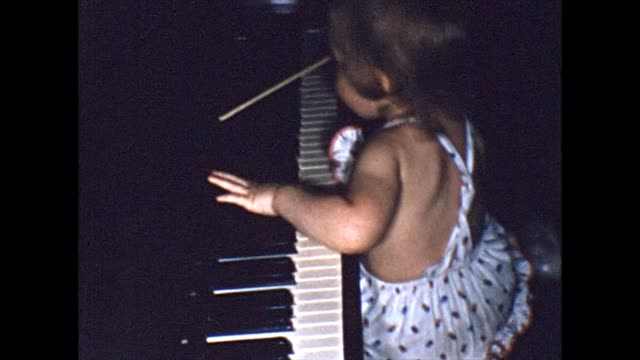 1955 toddler climbing and playing on piano - collaboratore domestico video stock e b–roll