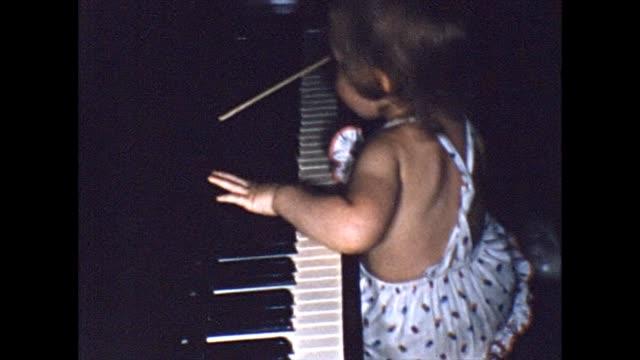 stockvideo's en b-roll-footage met 1955 toddler climbing and playing on piano - huishoudelijke dienstverlening