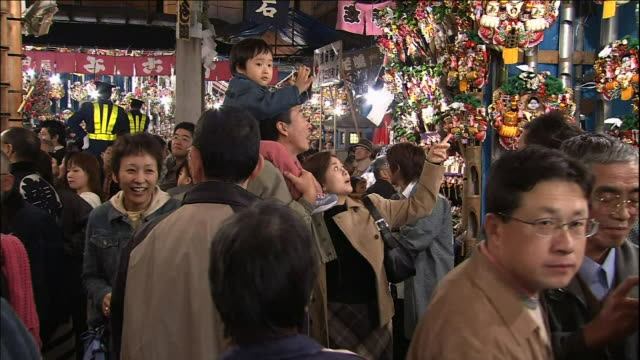 A toddler clings to his father's head at Ohtori Shrine.  Tori-no-Ichi