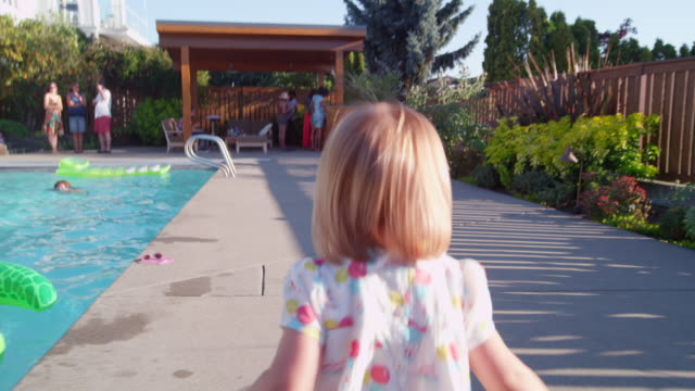ms ts toddler daughter running along pool deck towards father sitting eating dinner during neighborhood pool party - daughter stock-videos und b-roll-filmmaterial