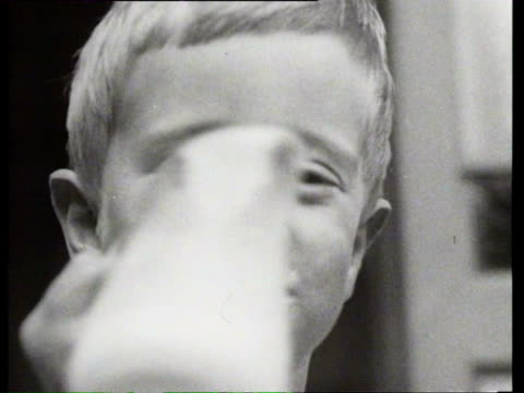 vidéos et rushes de 1923 b/w toddler drinks milk from small pitcher / amsterdam, netherlands - 1923