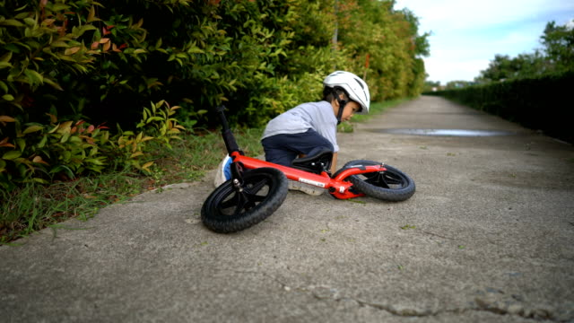 toddler falls off balance bike. - sollevare video stock e b–roll
