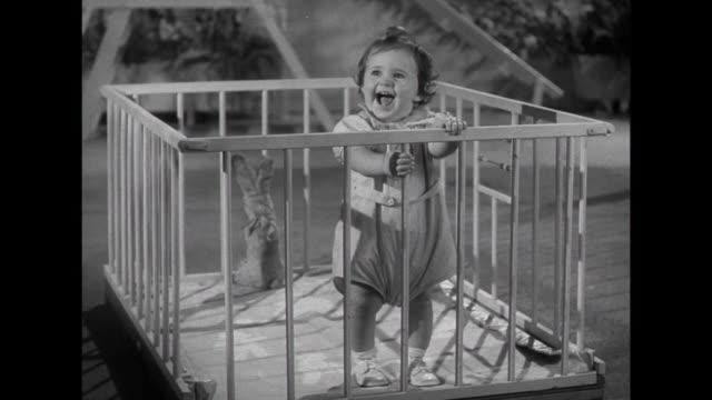 stockvideo's en b-roll-footage met 1941 a toddler giggling in playpen - 1941