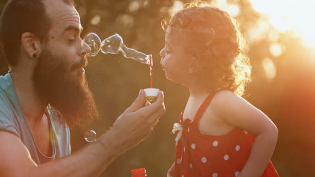vídeos de stock e filmes b-roll de slo mo toddler girl blows bubbles into father's face in the setting sun - soap sud