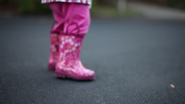 A toddler girl dances outdoors in her pink rain boots.
