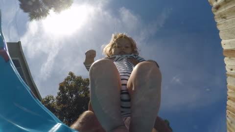 vídeos de stock, filmes e b-roll de a toddler girl dipping her toes into a small pool outside on a sunny day. - molhado